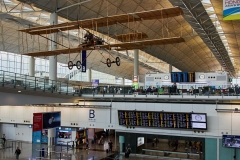 The Wright Brothers plane hangs from the roof with the check-in counters above the arrivals hall.